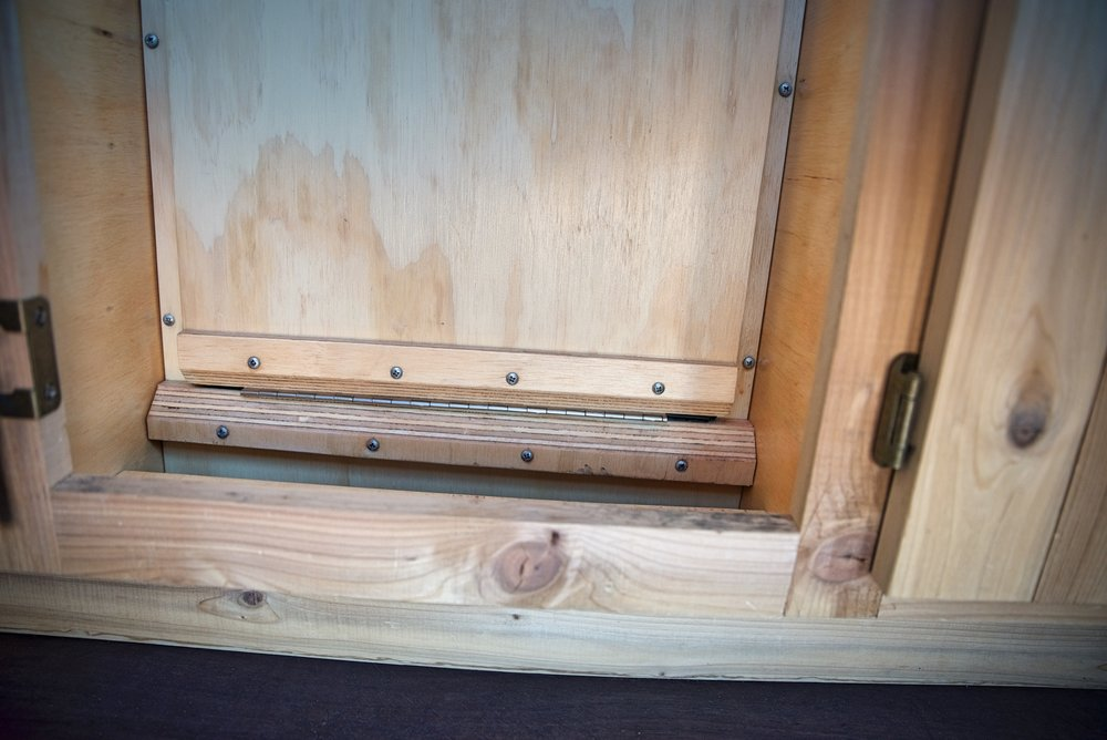 We added these two angled pieces of wood around the hinge to reinforce the places where we had accidentally split the plywood a bit when attaching the hinge.