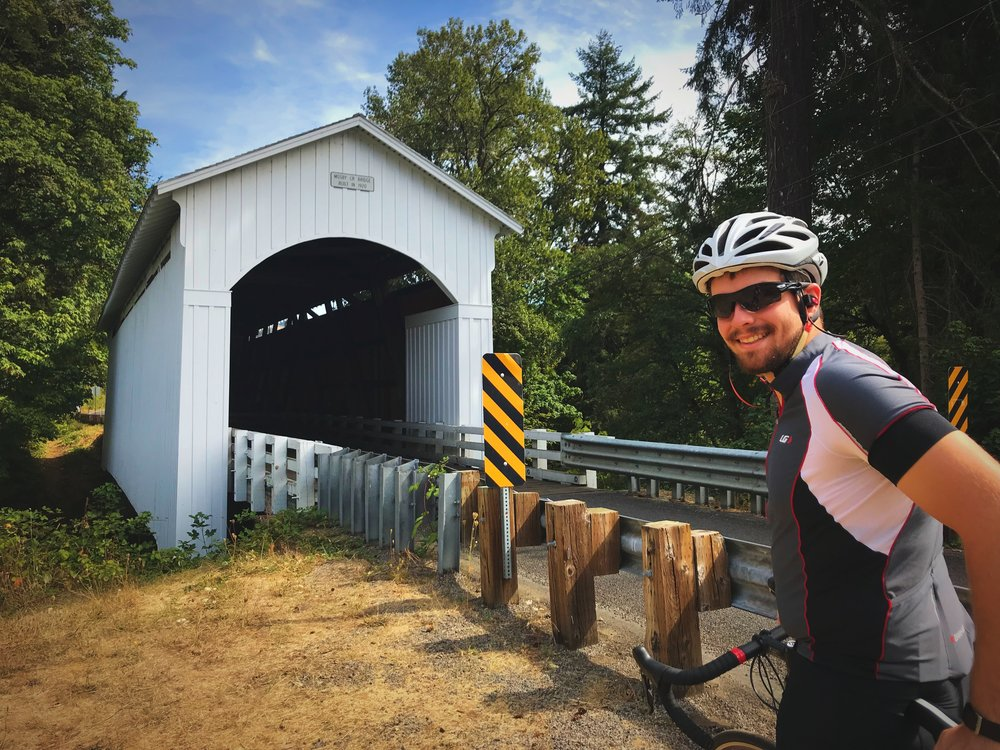 Ian posing by the picturesque Mosby Creek Covered Bridge along the Covered Bridges Scenic Bikeway near Cottage Grove, Oregon.