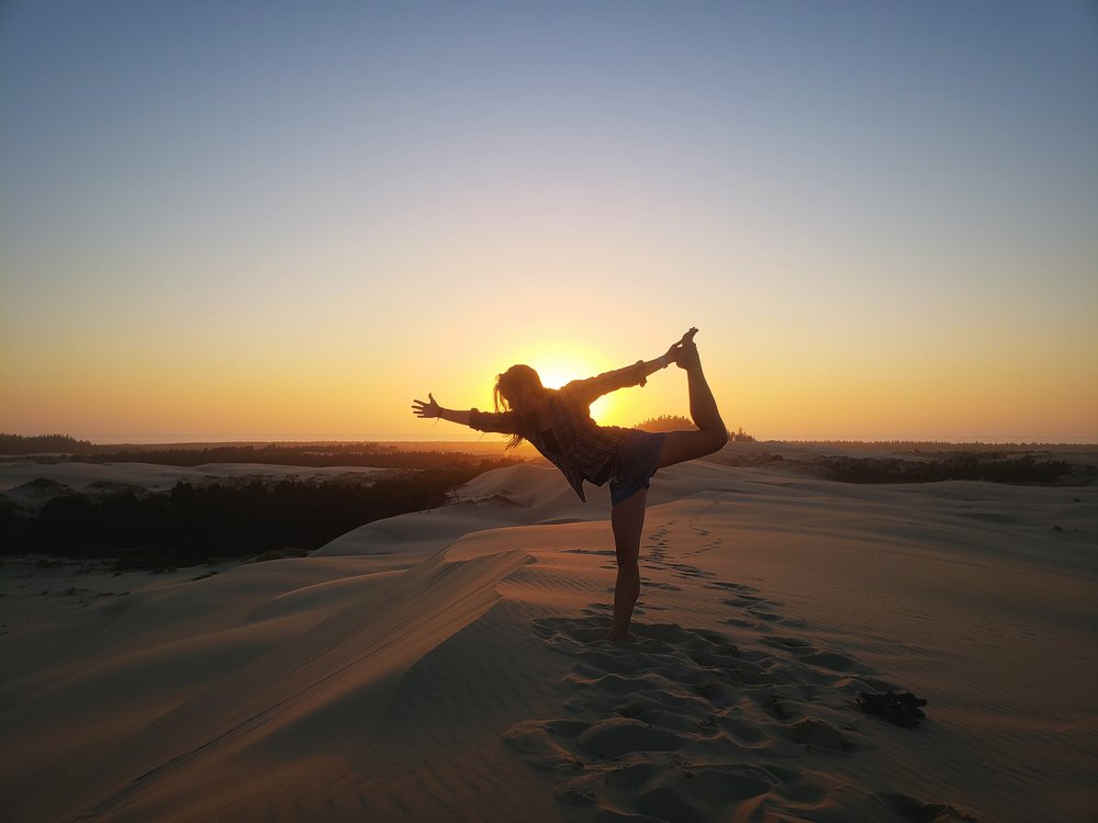 Striking a pose on the top of the tallest dune as the sun sets over the ocean.