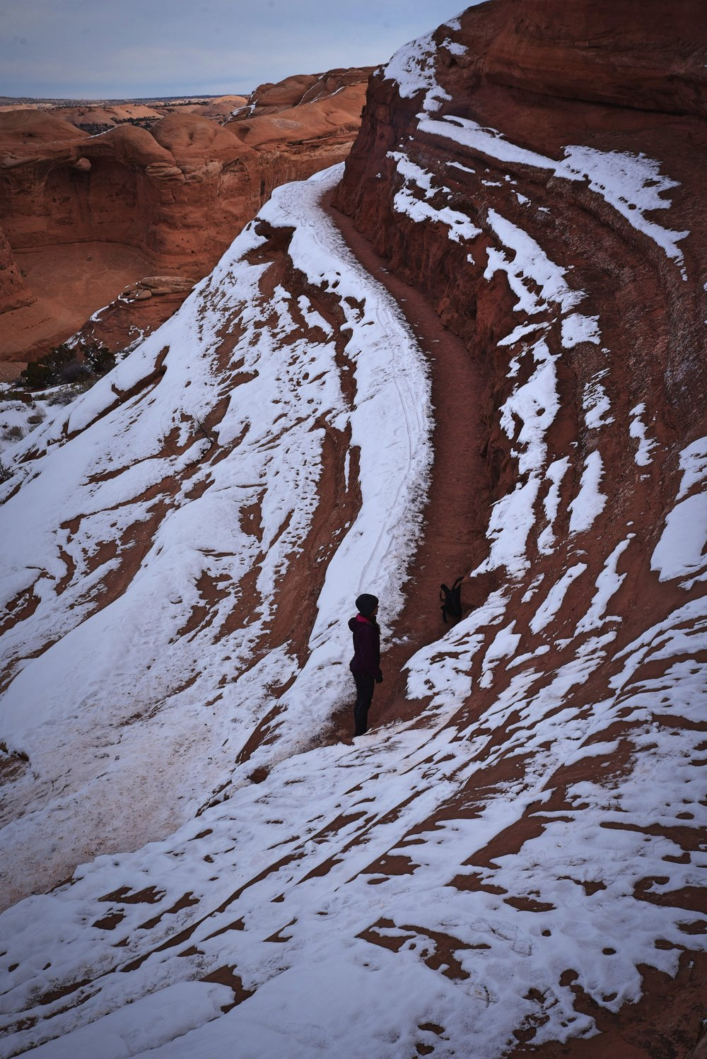 The final portion of the Delicate Arch Trail is on a ledge along a rock wall.