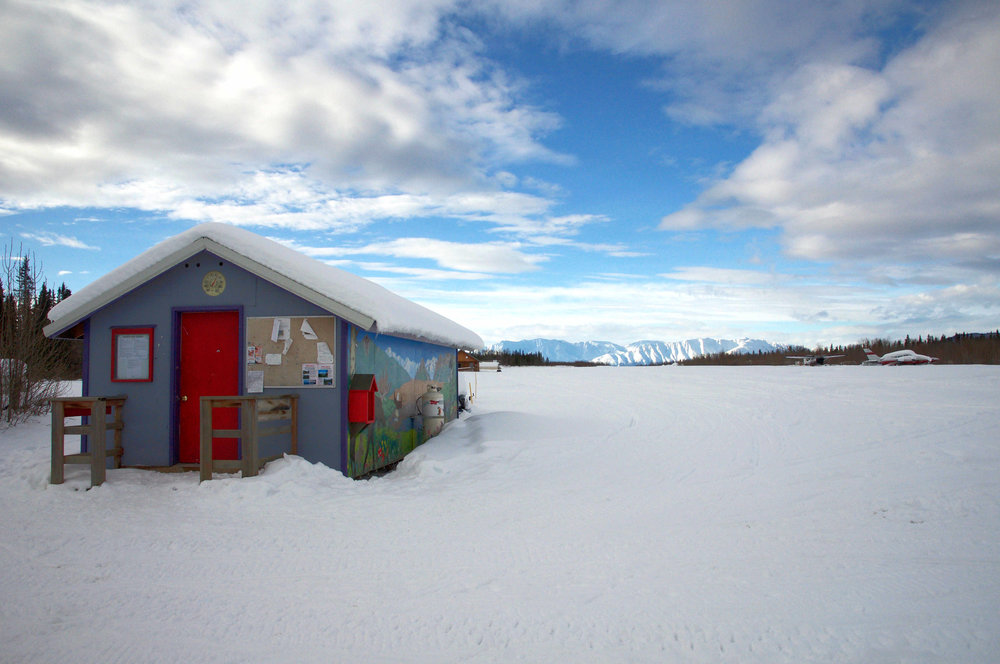 The Chugach Mountains highlighted behind the mail shack.