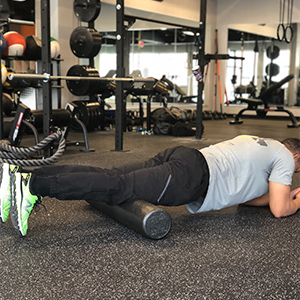 To begin foam rolling the quads, place the top of the knees on the foam roller while assuming a plank position. Start with both legs on the roller to gauge how much pressure you prefer.