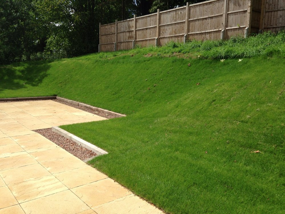 Banked lawn with oak sleeper edging, stone chipping and buff, riven concrete slabbing