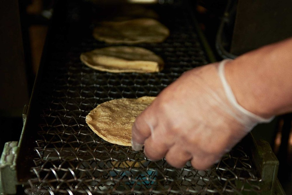 Cooking: - The dough is hand-fed through the tortilla press where it is cut into tortilla sized circles and cooked.