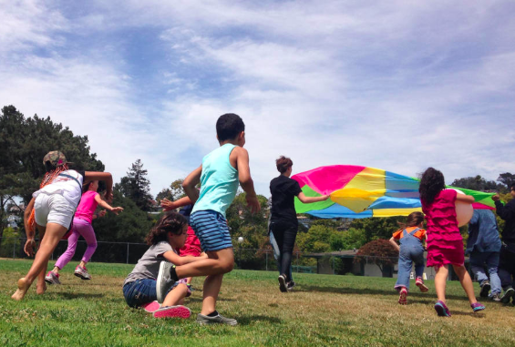 Kids play with a parachute at Rainbow Day Camp in El Cerrito. (Photo: Sandra Collins)