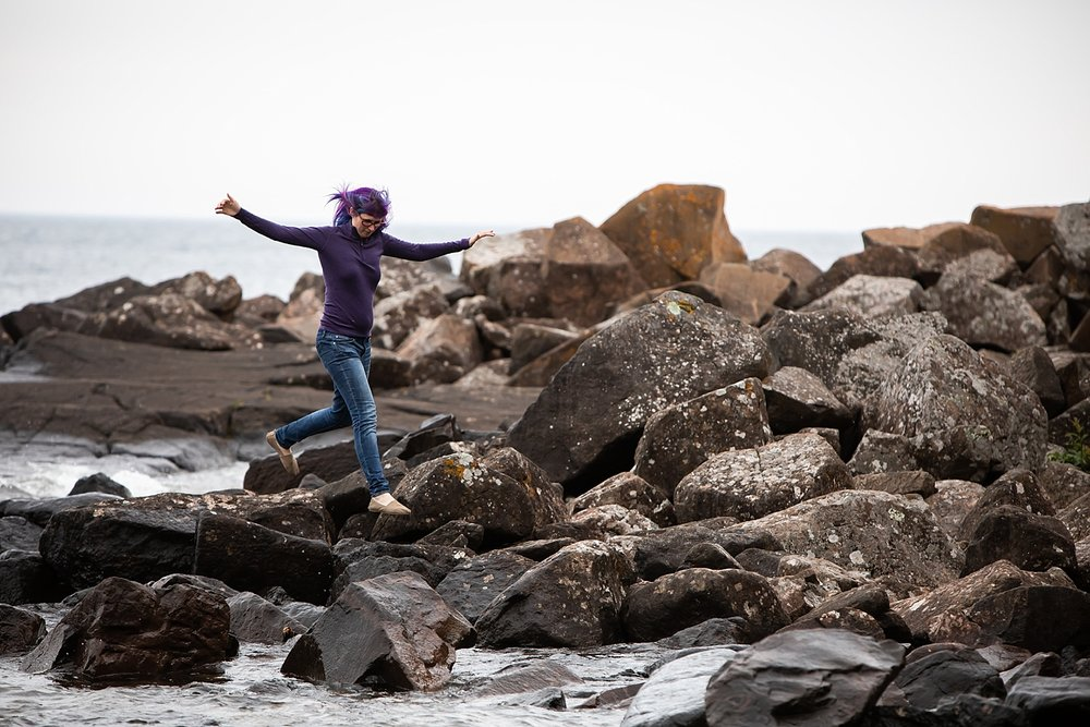 personal brand photograph of jamie swanson jumping over coastal rocks