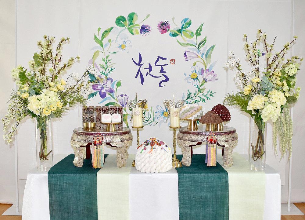 그린 리스(green wreath) - Included: Green Wreath backdrop, 2 pearl small table, linen runner, 5 high quality brass plates, 2 butterfly brass candle holders, display rice cakes, dates, fruits,2 flower vases, display, mini premium pearl accessories, traditional ornaments, shil ta rae, traditional shoes그린리스 1단 상품구성: 현수막, 1단 테이블, 자개상 2개, 모시 러너, 방짜유기 5개, 유기나비촛대 2개, 모형 삼색한과, 대추, 수수팥떡,백설기, 과일들,꽃과 화병 2개,상화, 미니 자개 병풍, 노리개, 실타래, 전통 꽃신 or 테사해
