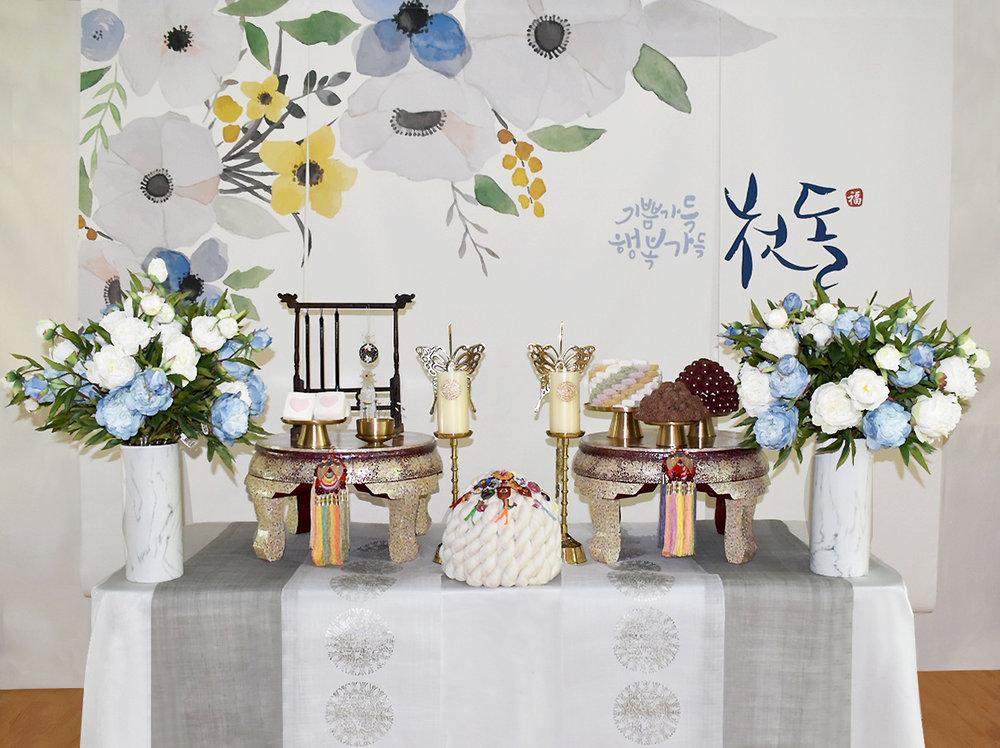마랑 그레이(Marang Gray) - Included: Marang Gray backdrop, 2 pearl small table, linen runner, 5 high quality brass plates, 2 butterfly brass candle holders, display rice cakes, dates, fruits,2 flower vases, display, premium brush rack, traditional ornaments, shil ta rae, traditional shoes그린리스 1단 상품구성: 현수막, 1단 테이블, 자개상 2개, 모시 러너, 방짜유기 5개, 유기나비촛대 2개, 모형 삼색한과, 대추, 수수팥떡,백설기, 과일들, 꽃과 화병 2개,상화, 프리미엄 붓걸이, 노리개, 실타래, 전통 꽃신 or 테사해