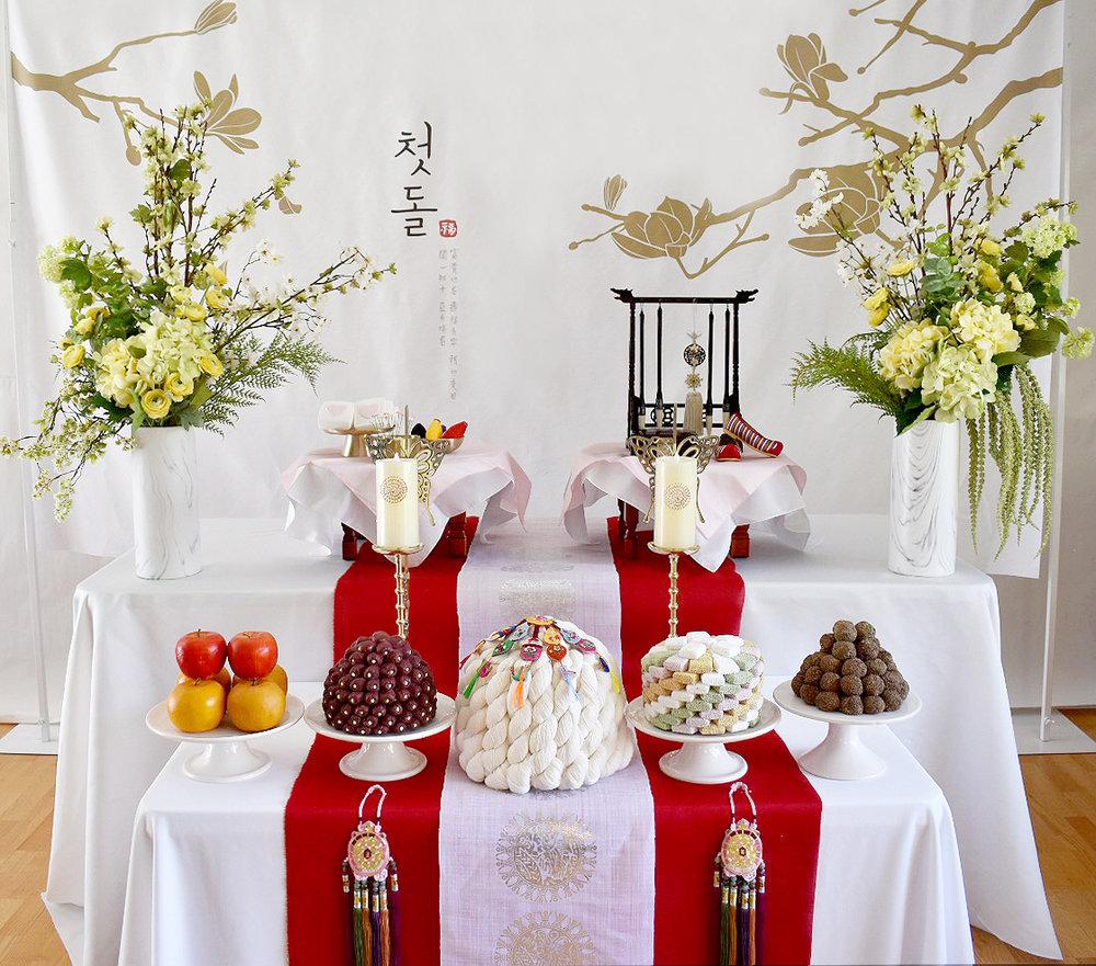 첫돌 레드 (red 1st Birthday) - Included: 1st Birthday backdrop, 2 layers table, 2 round small table, round traditional table covers,linen runner, 6 plates, 2 butterfly brass candle holders, display rice cakes, dates, fruits, 2 flower vases, display mini flowers, premium brush rack, traditional ornaments, shil ta rae, traditional shoes상품구성 : 현수막, 2단 테이블, 원형상2개, 모시 러너, 방짜유기 3개, 사기 그릇 4개, 유기나비촛대 2개, 모형 삼색한과, 대추, 수수팥떡,백설기, 과일들,꽃과 화병 2개,상화, 프리미엄 붓걸이, 노리개, 실타래, 전통 꽃신 or 테사해