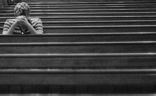 young-man-praying-in-one-of-several-rows-of-pews.jpg