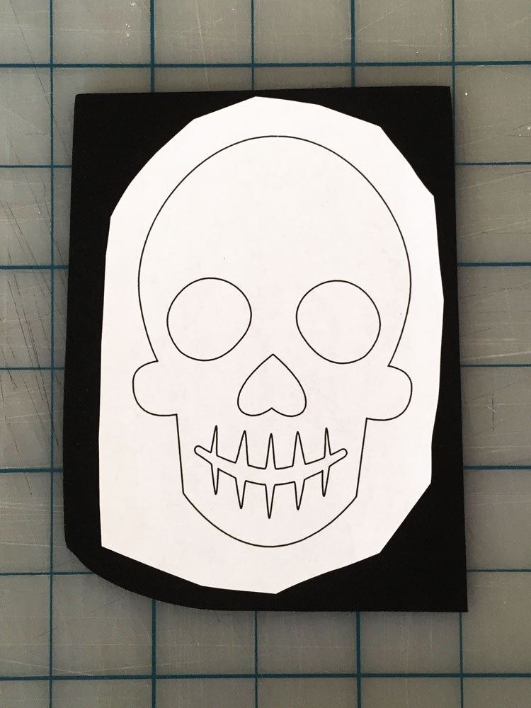 STEP 1: Lightly glue the skull template to the black foam sheet.