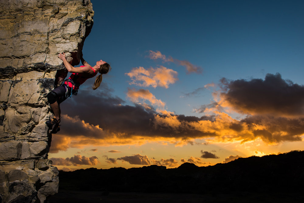 Athlete Camille King climbing a rock face on Portland, Dorset with sunset behind