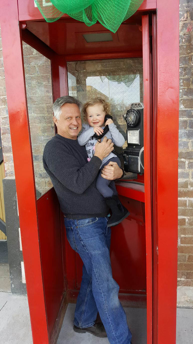 David and his granddaughter, Blair, in the telephone booth outside a building he is renovating.