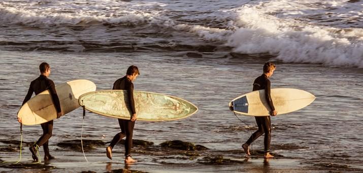 teenage-boys-heading-into-the-waves-to-surf.jpeg