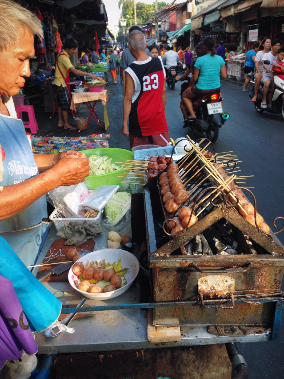 """It is impossible to describe the smell of Bangkok. The scent wafting through the streets changes from moment to moment. At any given second the hot breeze may change to the distinct aroma of sewage, before the wind takes it away and replaces it with the smell of sickeningly sweet pineapple and mango being sold from a nearby cart.  Street food is the everywhere. Old women stand hunched over large black woks crackling and popping with hot oil as they drop in chicken legs or whole crabs. Sausages lay piled up on trays in the sun, manned by someone with a fan to keep the flies off, causing you to wonder how long the meat has been baking in the heat of the day.  Chicken. There is a lot of chicken. Every single body part is fried in every single way and then either hung up, splayed out, or piled high onto platters for customers willing to pay the 80 baht. The streets are alive with shoppers and purveyors striking a deal or bargaining for their dinner. Vendors hand over organ meats on sticks or ladle vegetables and sauces into individual plastic bags for to go orders. People eat either standing on the corner, as they walk, or crowded around little plastic tables while motorbikes whiz past, babies riding in the front. Skinny cats with loosely hanging utters lay asleep, flopped across shelves holding the condiments used for the food. Passerby's stop to say hello to friends and nobody has a problem with staring at the lone """"farang"""", foreigner as they call out to me like they are playing a game of where's Waldo. It's too hot outside for me so I carry a large icy Chang Beer that has almost as much condensation on the glass as I have sweat dripping down the back of my neck. I pause here and there and take a swig while I contemplate taking the risk on those unique tiny bright blue mussels that are being steamed in heaping mountains, or those clams sitting in a spicy red stew of a broth."""