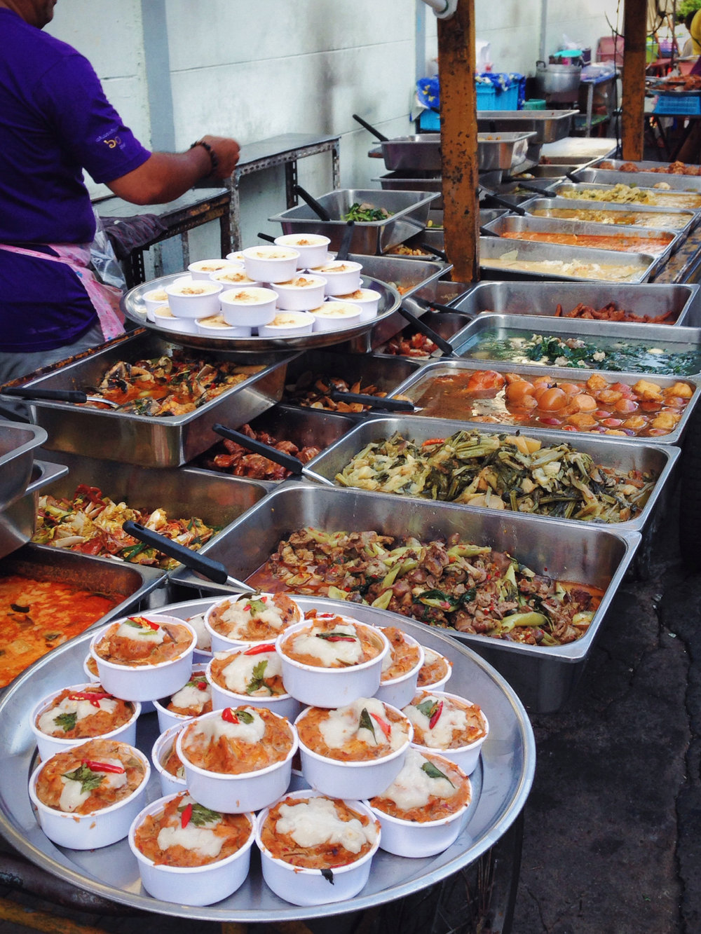 My culinary schooling and serve safe certification screams at the forefront of my mind as I take in the hunks of raw skewered meat and vegetables sitting mixed together on a bare and lonely table, as well as the plastic hotel pans of seafood lined up, almost certainly left out for more than four hours in the danger zone. But I'm hungry and curious, I can't resist. It's just too exciting, the area is too alive. Maybe it's the sight of all these new and exotic little foods beckoning to me. Maybe it's the noise, the sounds of cars, bikes, babies, and music swirling all around the cramped little streets producing It's own heartbeat. Or maybe it's the smell. The streets of Charoen krung 85 with it's dank heat that absorbs all the scents of fresh fruit, stinging spices, grilled goods and nearly soured meat- and leaves it hanging in the air around me. It's the smell of Bangkok.