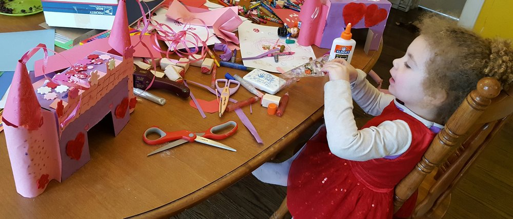 Evelet is enjoying indoor crafts by making Valentines Day castles from cereal boxes. I love the cones with the ribbon coming out the top! …and the cute hearts and flowers.
