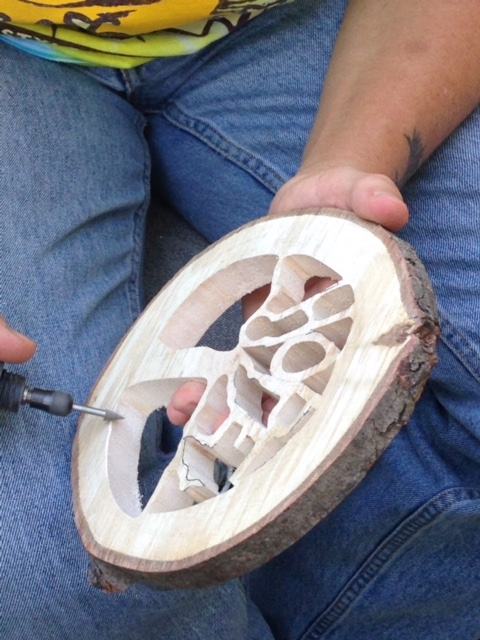 Then she uses a rotary carving tool to add details and sand the tree.