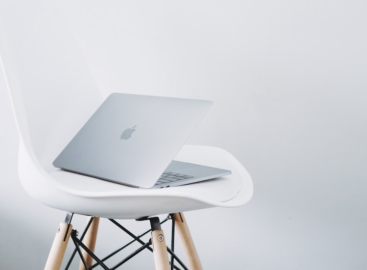 Apple Computer Sitting on a White Chair