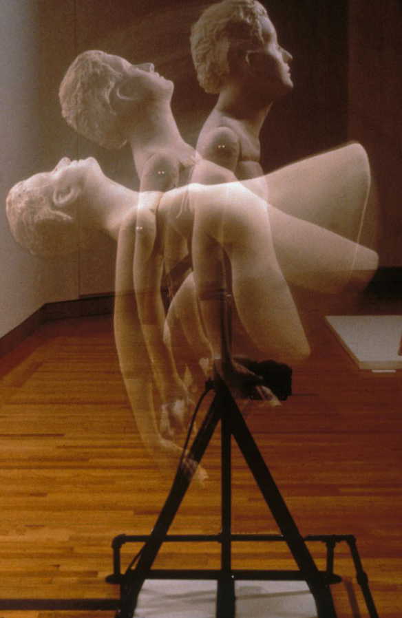 PLUMB (1999) / Level Best®, motor (which continuously tilts the figurative element from horizontal to vertical and back again), blinking doll eyes, fabric, hankies, 52 x 40 x 46""