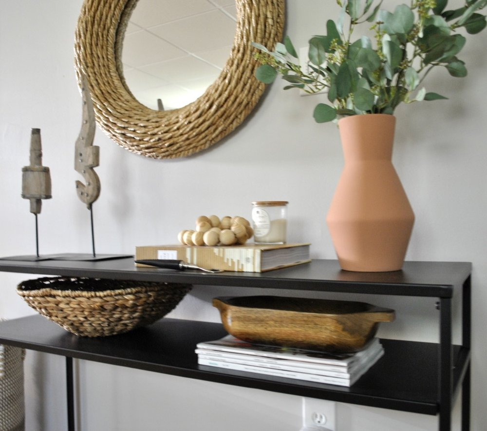 Basement console table with terra cotta vase and other organic details.