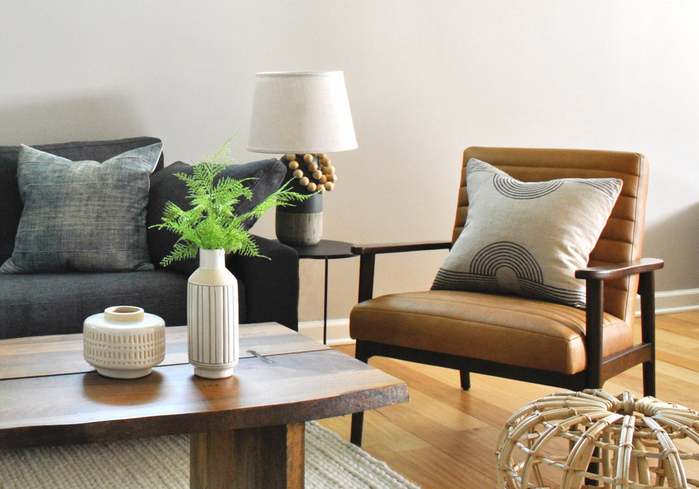 Light and bright basement remodel with light wood floors and mid-century style leather chair.