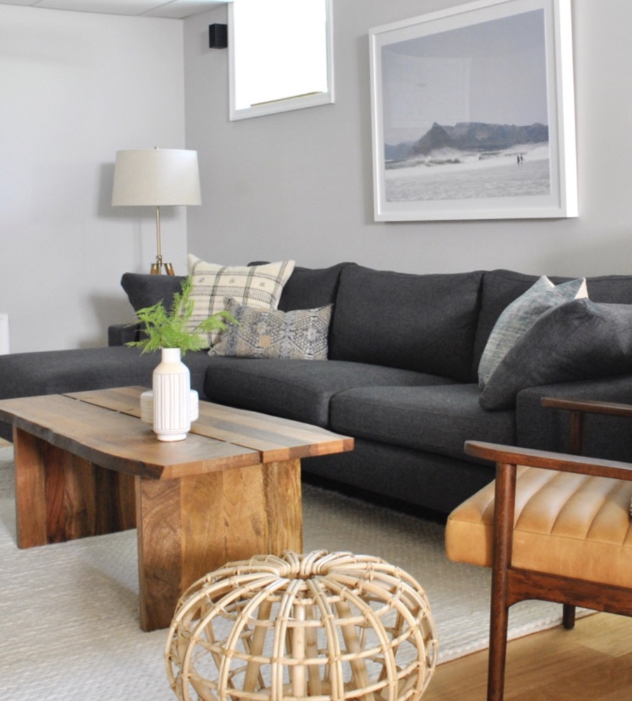 Basement family room with live edge coffee table and vintage pillows.