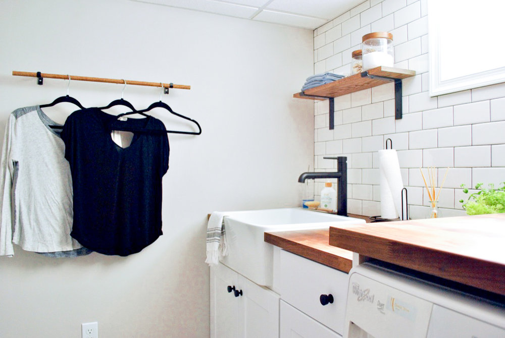 Laundry room with clothes rack, farmhouse sink and white subway tile.