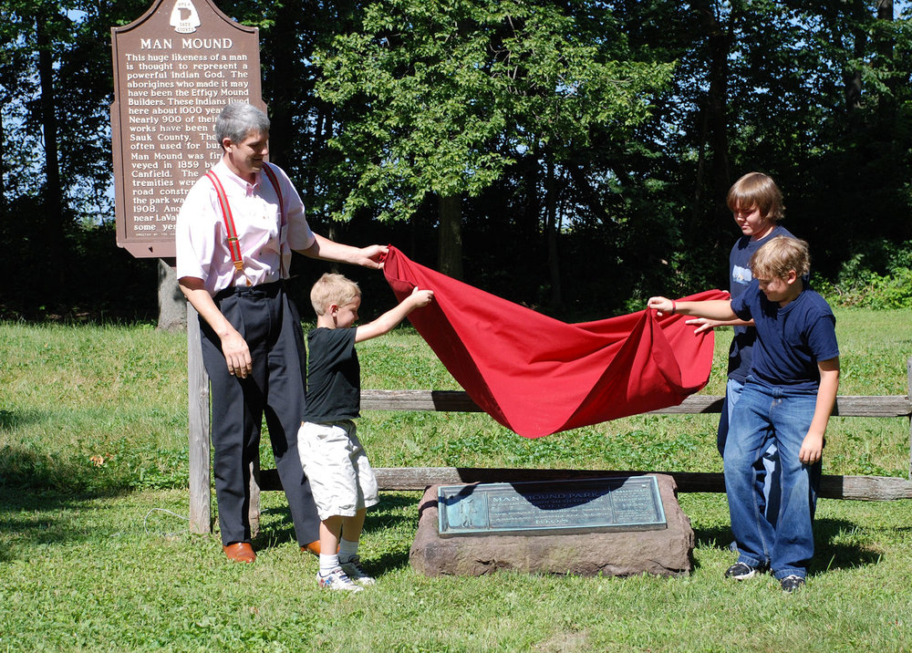 Lucas Van Orden and his sons unveil the plaque which his great grandfather helped erect in 1908.