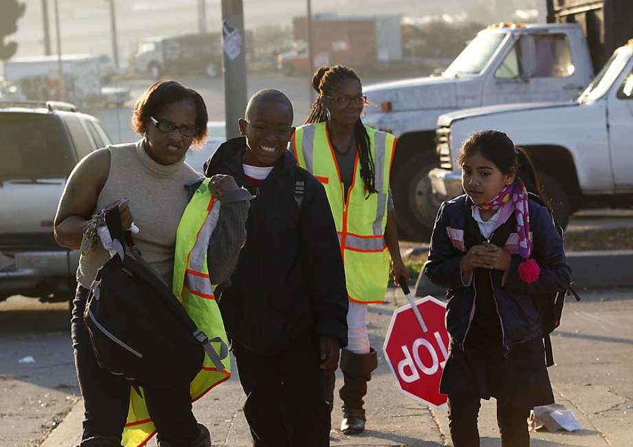 Uzuri Pease-Green (left) and her daughter, monitor Urell Pease, knock on doors to pick up children and walk them safely to school in San Francisco.