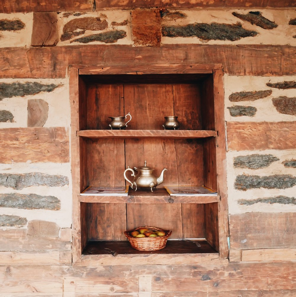 A very cute shelf inset in recycled wood, mud and stone walls.