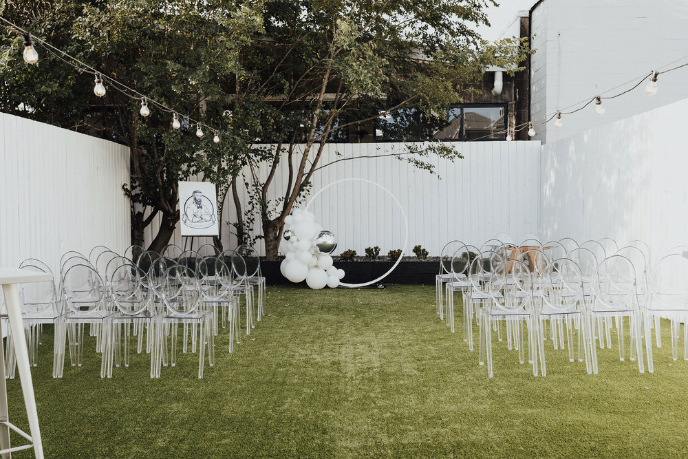 Ceremony Set Up - We loved this minimal setting featuring a neon ring arbour from Event Letters!