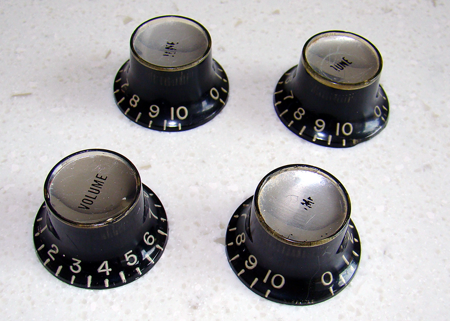 "BLACK TIN KNOBS 1961-68  Set of four Gibson black ""reflector"" knobs. These are a matched set in excellent vintage condition. No cracks or damage. They have the silver coloured tops. We also have gold tinted tops, please ask.  Price: POA"
