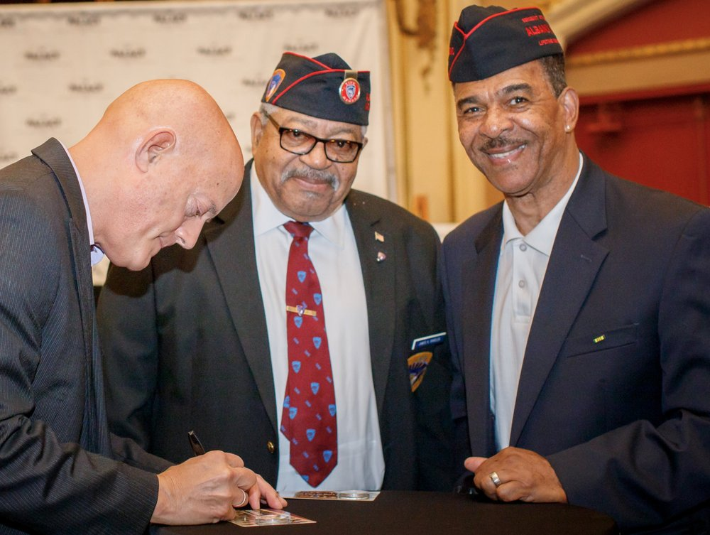 Chris Costello, left, signs Sgt. Henry Johnson commemorative package for Albany veterans of the 369th Regiment during the premiering event at The Palace Theatre, July 23, 2018.