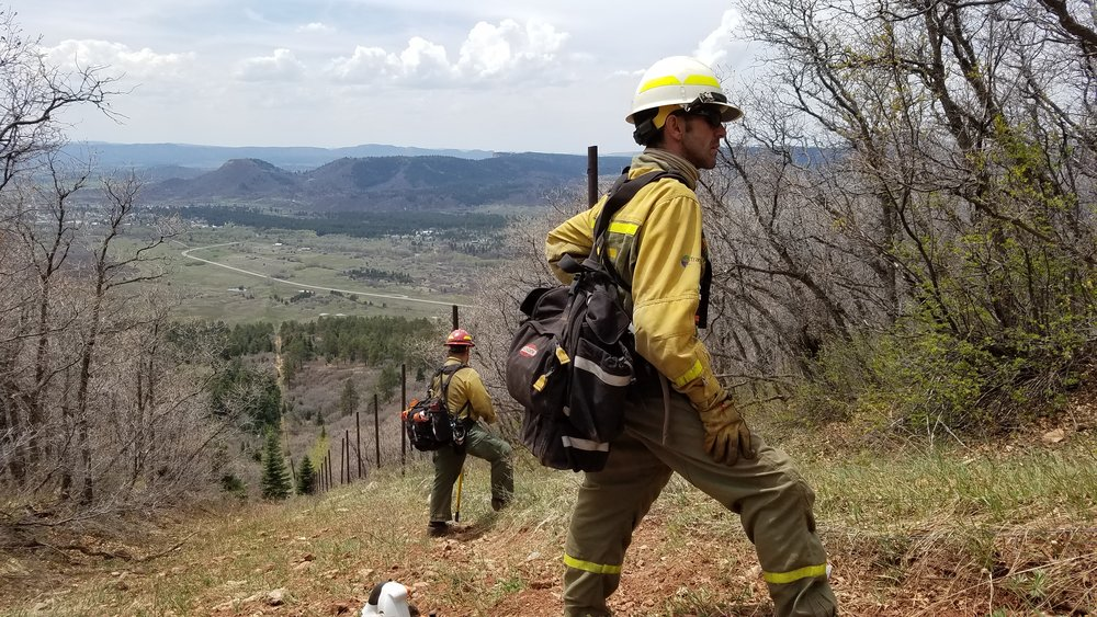 Two firefighters monitor the burn from the fire line during a TREX in Chama, NM in May 2017.