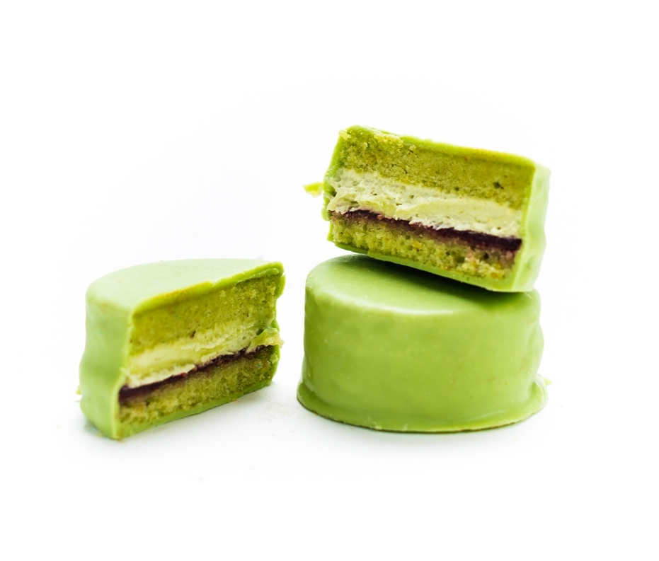 Pistachio Raspberry   Savory and sweet meet in this delightful marriage of fruit and nut. Nutty pistachio cream filling and tangy raspberry jam sit within a sandwich of pistachio cake and green-tinted white chocolate.