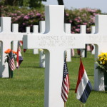 The white cross headstone of Cpl. Lawrence F. Shea in the graveyard at Margraten.
