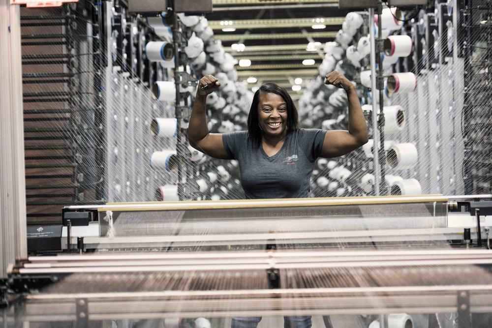 Fairystone Fabrics employee smiling beside factory equipment