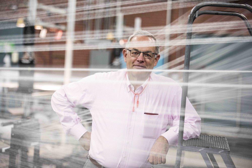 Fairystone Fabrics President Jim Bryan standing beside factory equipment