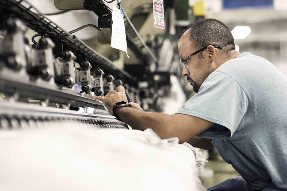 Fairystone Fabrics employee working on factory equipment