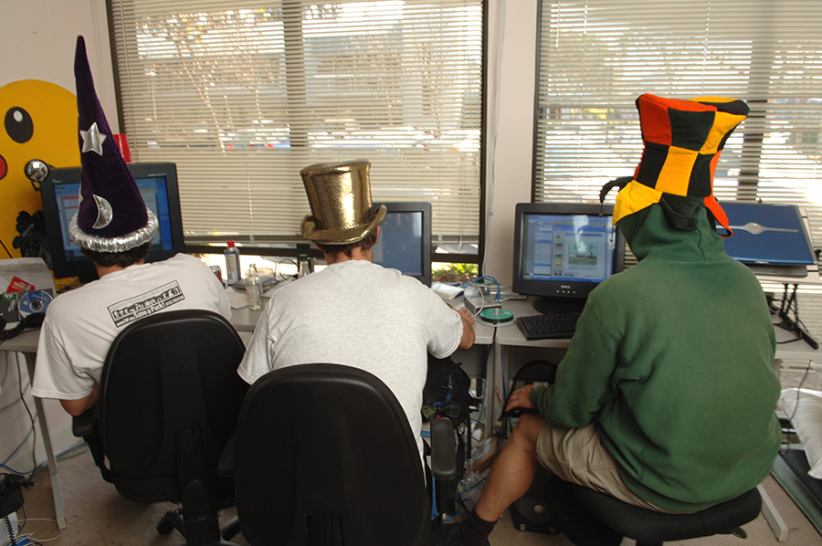 Grouper programmers hard at work in their cramped office space - donning their hats for their weekly 'silly hat day'!