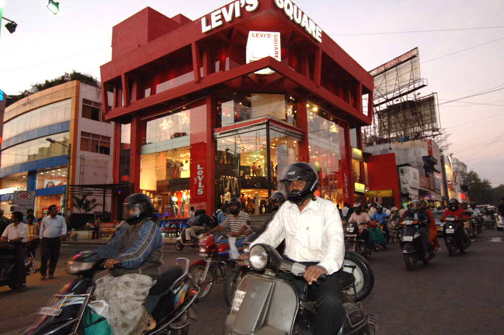 Mopeds streaming down Bangalore's premium shopping road - Brigade Road. The money men are responding to the increased spending power in Indian cities such as Chennai and Bangalore.