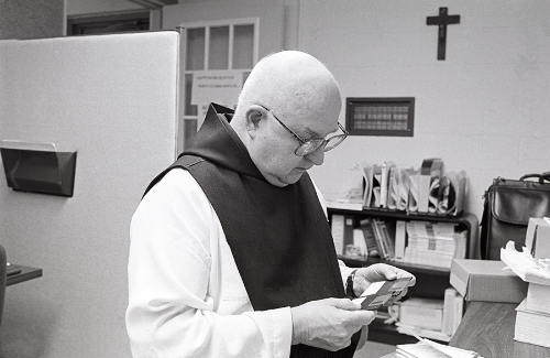 Father Paschal Balkan studying the back-up disks.