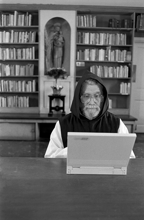 Brother Benedict Simmonds on his lap top in the Monastery library.