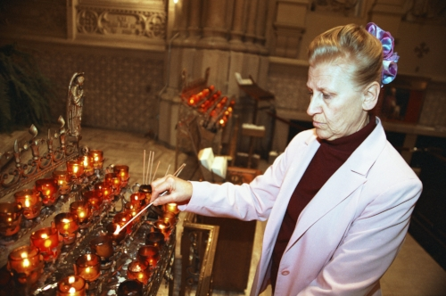 Shirley Tice lighting a candle at St. Patrick's church in New York City who credits her faith and the Gerson therapy with her remarkable cancer recovery.