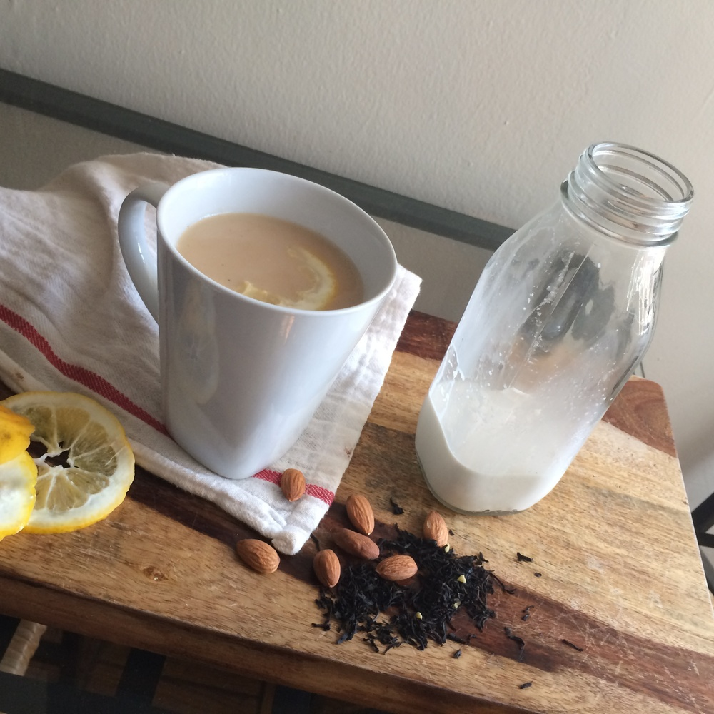 This  Roasted Vanilla Almond Milk  not only showcases the almond milk, but also gives a hint of how to use it: simply mixed in a hot cup of tea with a slice of honey. The wood background, looseleaf tea, homely tea towel, and whole almonds also contribute to the rustic styling of this photo.