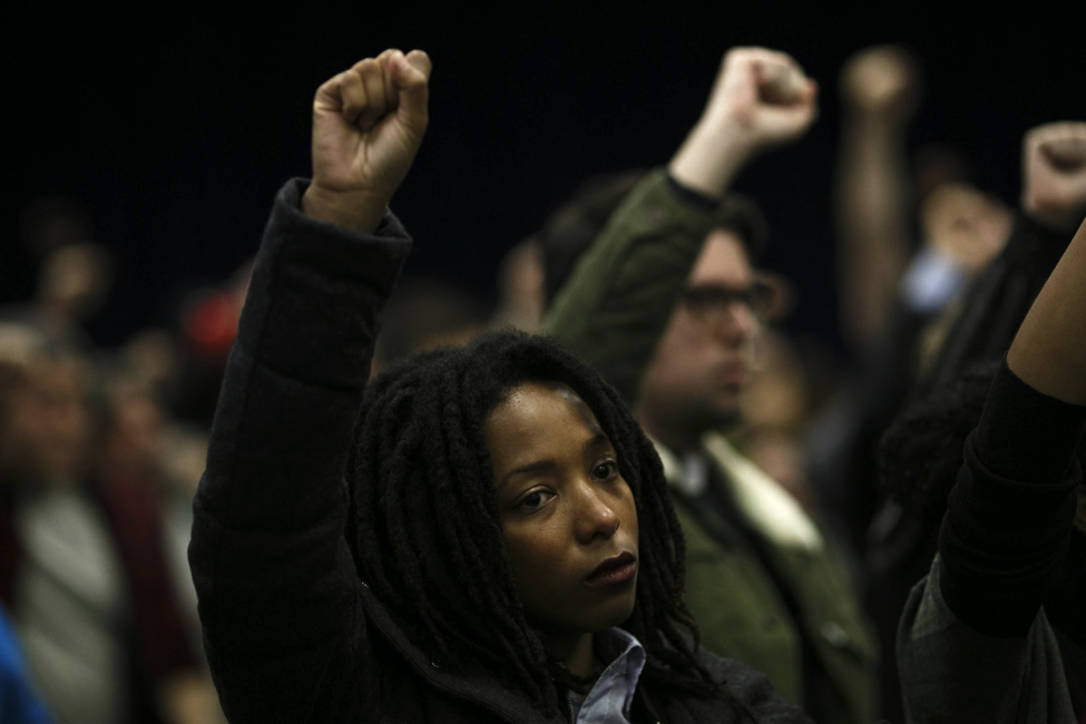 Attendees raise their fists in protest during the November Police Board meeting Thursday. (Photo: Jonathan Gibby)