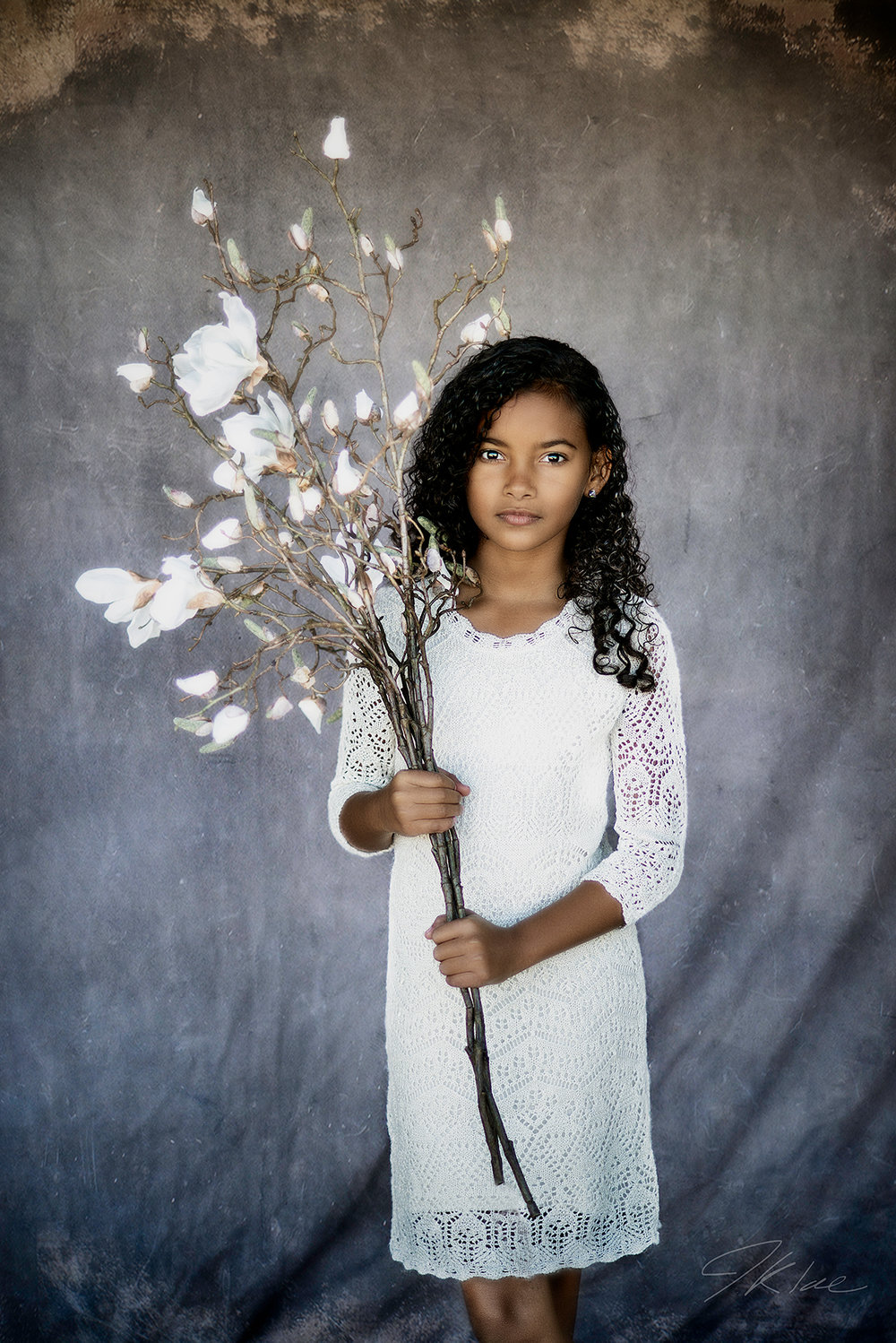 Fine Art Children's Portraiture of girl in whit dress holding white flowers in McKinney Texas