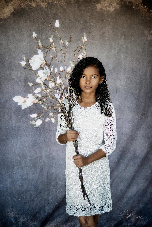 Fine Art Children's Portraiture of girl in whit dress holding white flowers in McKinney Texas