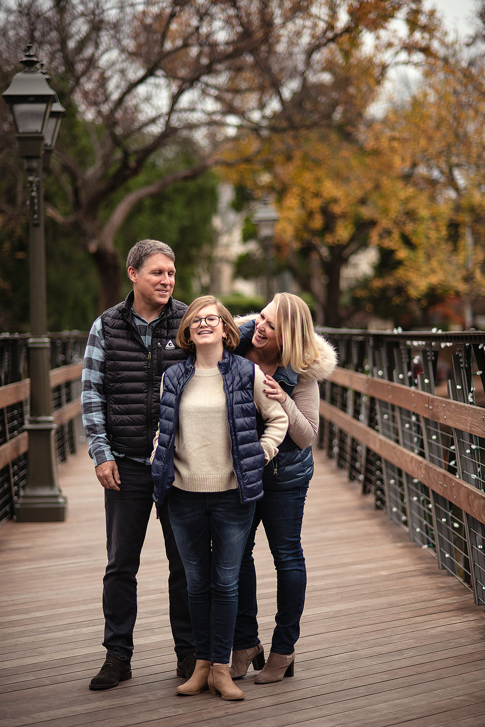 Fun Family Portrait of family laughing together on bridge in Highland Park Texas